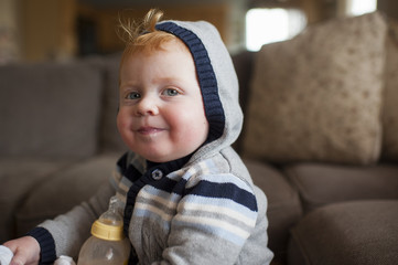 Portrait of cute baby boy with milk bottle wearing warm clothing in living room at home