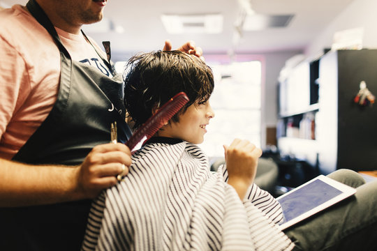 Side view of barber cutting boy's hair at salon