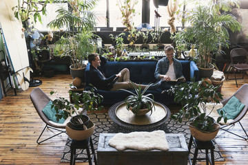 Homosexual couple relaxing while sitting on sofa amidst potted plants at home