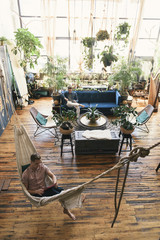 High angle view of gay man relaxing in hammock while boyfriend sitting on sofa at loft apartment