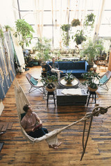 High angle view of gay man relaxing in hammock while boyfriend sitting on sofa against potted plants at home
