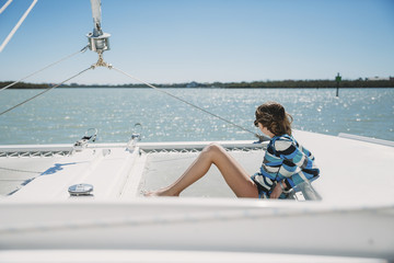 Side view of girl sitting in boat on sea against clear sky during sunny day