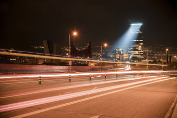 Light trails on road in illuminated city at night