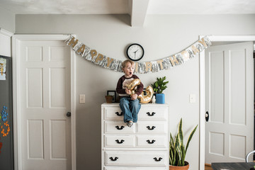 Birthday boy with number balloon sitting on cabinet at home