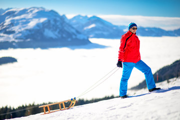 Young attractive man ready to go sledding in Swiss Alps during winter vacation.