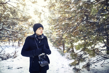 Young man with vintage camera wearing black warm clothing amidst forest during winter