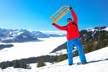 Young attractive man ready to go sledding in Swiss Alps during winter vacation