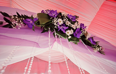Original wedding floral decoration and bouquets of flowers hanging from the ceiling. Tender purple, white and pink colors. Wedding arch and wedding chairs