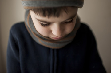 Close-up of boy wearing warm clothing at home