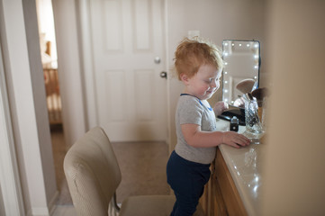 Side view of cute baby boy standing by beauty products on chair at home