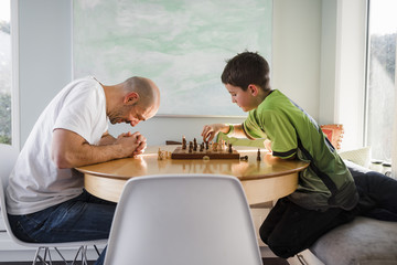 Father with son playing chess on table at home