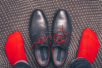 A man is wearing classic leather shoes with red laces and in red stylish socks, buying shoes, a first-person view