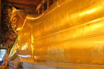 Long body of Reclining Buddha golden statue. Wat Pho (Wat Phra Chetuphon Vimolmangklararm) of Buddhist temple, Bangkok, Thailand.