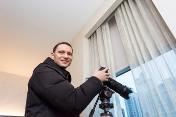 Young happy smiling man photographer with tripod taking pictures inside room of hotel, apartment building through window in New York City, NYC urban