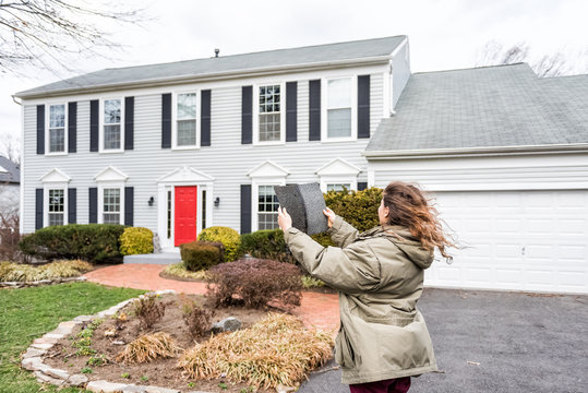 Young woman, female homeowner standing in front of house on windy day in coat jacket during storm holding up roof tile shingle inspecting damage