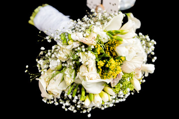 Wedding bouquet with many flowers, green yellow lily isolated lying on black table background macro closeup floral arrangement