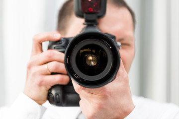 One young wedding photographer, ring, in dress shirt standing with camera, external flash, taking pictures macro closeup of lens, reflection