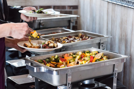 Hot buffet tray, fresh grilled vegetables with closeup of woman using tongs to serve food to plate in banquet, wedding, or restaurant inside