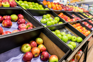 Many varieties assorted apples on display shelf in grocery store boxes in aisle, supermarket inside, nobody, including granny smith green and macintosh red fruit