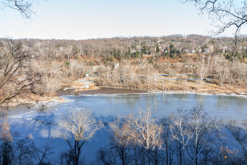 Overlook of Potomac River frozen surface in winter landscape, bare trees with Washington DC neighborhood houses, park, Fletcher's Cove, close to Georgetown in capital city