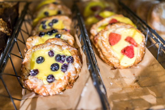 Closeup of many yellow cream cheese berry fruit blueberry and strawberry baked danish pastries on shelf tray display desserts in bakery shop cafe store rustic