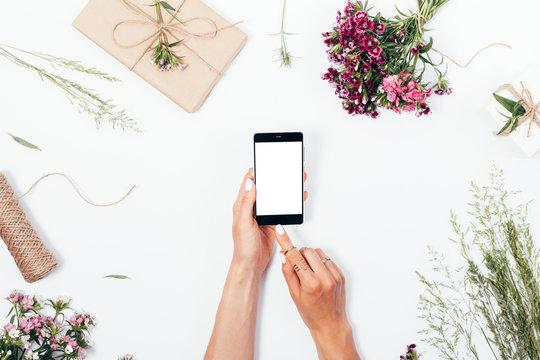Woman uses smart phone among rustic gifts