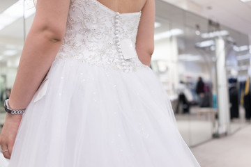 Closeup back of young woman trying on zipper zipped button wedding dress in boutique discount store with shiny tulle, price tag, engagement ring, fitness watch