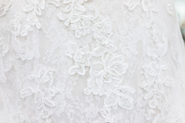 Macro closeup of lace wedding dress veil material, white garment textile with shiny rhinestones design