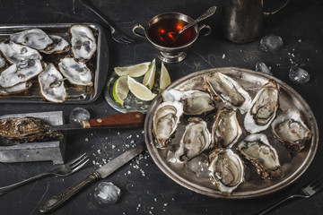 Plate of open oysters on ice with vinegar souce and lemon