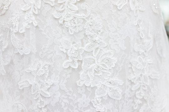 Macro closeup of lace wedding dress veil material, white garment textile with shiny rhinestones design