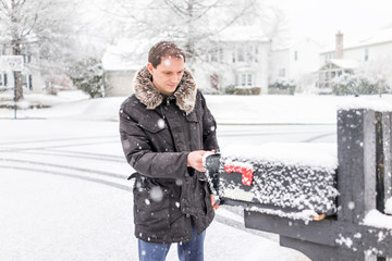 Young man checking mail in neighborhood road with snow covered ground during blizzard white storm, snowflakes falling in Virginia suburbs, single family homes in mailbox box