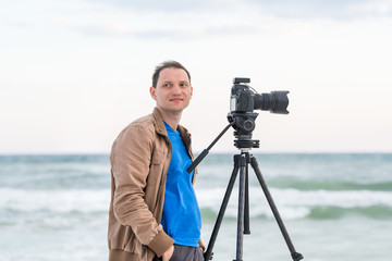 Young man professional photographer taking pictures and video of beach sunset in Florida panhandle, with jacket, wind, beach waves, tripod