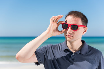 Young handsome attractive man hipster millennial serious face closeup on beach during sunny day with red sunglasses in Florida panhandle with ocean