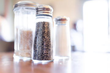 Macro closeup of salt, pepper and brown raw sugar shakers in bottles on wooden table in rustic restaurant