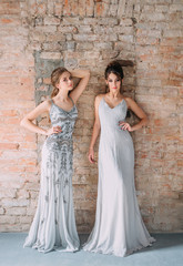 Two young girls in gray, long, shining, evening dresses with rhinestones and stones. The image of schoolgirls at the prom. Festive make-up nudes and smokies eyes. High, collected hairstyles.