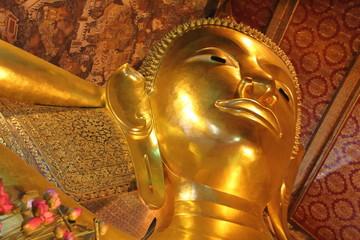 Face of Reclining Buddha golden statue. Wat Pho(Wat Phra Chetuphon Vimolmangklararm) of Buddhist temple, Bangkok, Thailand.