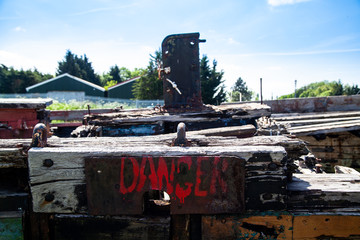 Danger sign on Rotting Wooden Structure of an old cargo  barge