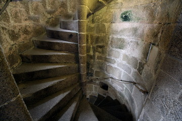 Old stone spiral staircase going up the inside of a castle tower.