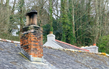 Old red brick chimney stack on a slate roofed building, with another old roof behind it and trees in the background
