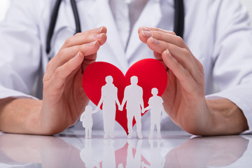 Doctor Protecting Family Cut Out With Heart Shape