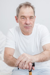 Sad senior man with a cane sits on a bed