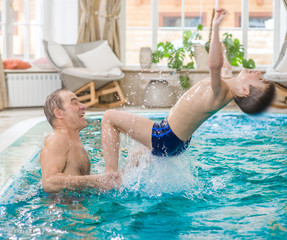 father having fun with his son in the pool