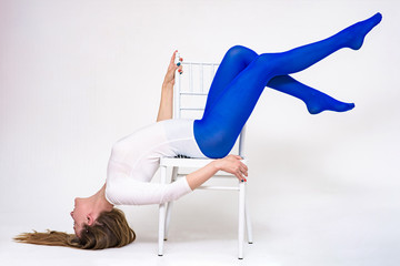 Portrait of a beautiful woman on a white background doing exercises on a chair.