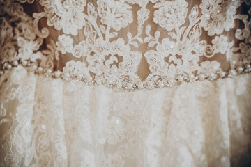 wedding dress detail. pearls and stone on floral gown, expensive cloths, rustic wedding morning preparation. space for text. luxury fabric