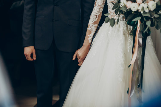 wedding couple holding hands close up at matrimony wedding ceremony in church. stylish bride and groom hugging. emotional moment, space for text. religion unity concept