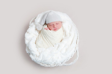 Newborn baby in white wrap laying on basket