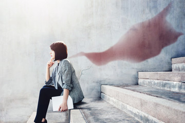Power, Success and Leadership in Business concept, Working Woman sitting on outdoor Stair and looking Forward with Superhero Blanket Shadow shade on the wall, Side view