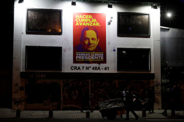 People walk past a poster of Colombian presidential candidate German Vargas Lleras hanging on the wall of a building, in Bogota