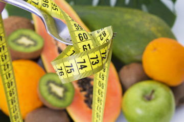 diet and slimming concept. fork with tape measure and tropical fruits
