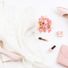 Fashion blogger workspace flat lay with pumps, silk top, cosmetics, purse and flowers.
